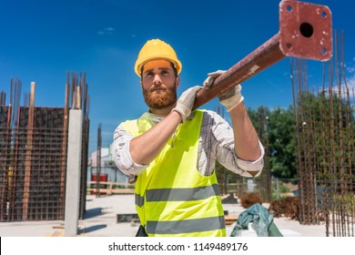 Full length of a blue-collar worker, wearing safety equipment while carrying a heavy metallic bar during work on the construction site of a residential building
