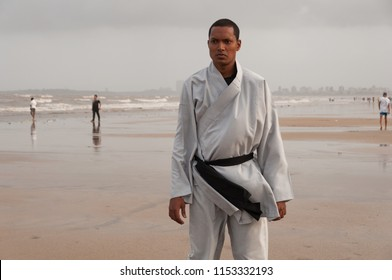 Full length body action shot of young Asian male Shaolin Kung Fu instructor training on Juhu beach, Mumbai. Intense concentration expression. Sand in foreground and grey sky in background.