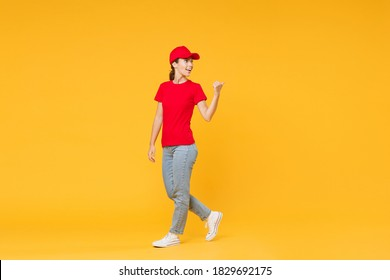 Full length body delivery employee woman in red cap blank t-shirt uniform work courier in service during quarantine coronavirus covid-19 virus standing isolated on yellow background studio portrait