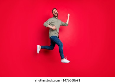 Full length body photo of cheerful playful happy glad handsome white trendy model rock musician wearing grey shirt imagining like playing guitar while isolated with red background