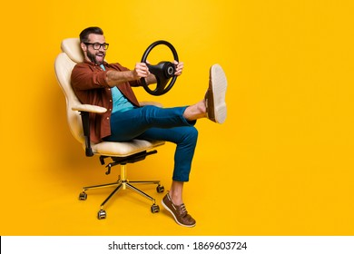 Full length body photo of happy fooling man in chair keeping steering wheel pretending car driver isolated vivid yellow color background - Shutterstock ID 1869603724
