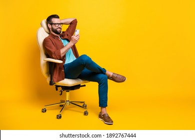 Full length body photo of smiling freelancer keeping smartphone social media sitting in chair pause isolated vibrant yellow color background