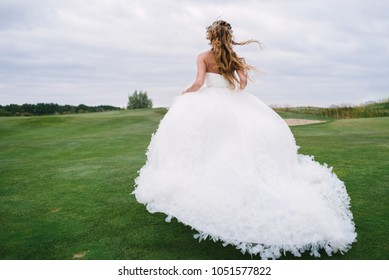 Full length body portrait of beautiful bride in fashion white wedding dress with feathers running away through green golf course, back view. Runaway bride, copy space