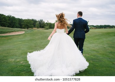 Full length body portrait of young bride and groom running on green grass of golf course, back view. Happy wedding couple walking through golf course, copy space
