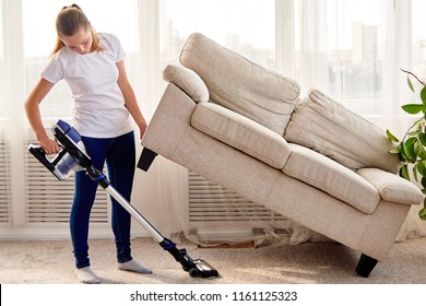 Full length body portrait of young woman in white shirt and jeans cleaning carpet with vacuum cleaner under sofa in living room, copy space. Housework, cleanig and chores concept