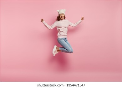 Full length body shot of joyful pleased young female model jumps happily in air against pink background, wears warm hat with ears, sweatshirt, jeans and sneakers, feels energetic and optimistic