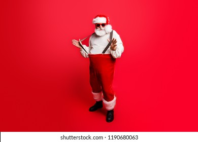 Full length body size of cheerful positive optimistic glad Santa pulling pants suspenders ready to feast festive party congrats congratulations best wishes sale discount isolated over red background