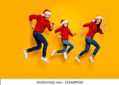 Full length body size of crazy smiling joyful happy family running for festive goods discounted wearing jeans denim red sweater santa cap headwear footwear speed fast excited isolated  color backgroun
