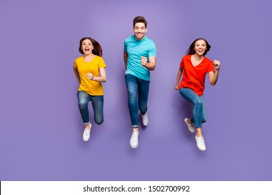 Full length body size front view photo of group of three crazy emotional hipsters models running to you wearing yellow blue t-shirts isolated violet background
