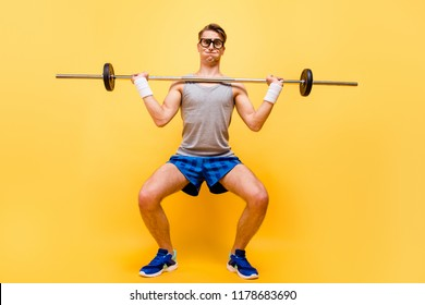 Full length body size of funky caucasian guy in glasses, doing physical exercises with dumbbell, isolated over bright vivid yellow background