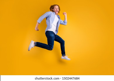Full length body size hoto of cheerful attractive handsome crazy hipster trying to gain as much speed as possible wearing jeans denim sneakers isolated over vivid color background