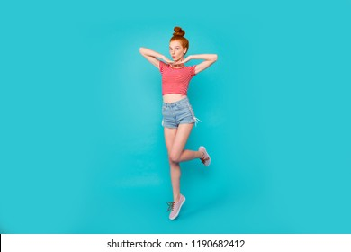 Full length body size of nice stylish adorable attractive pretty cheerful playful red-haired girl with bun, wearing jeans shorts and t-shirt, flying up in air, isolated on bright vivid blue background