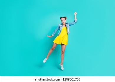 Full length body size of nice crazy amazed positive childish comic trendy girl with hair-buns, wearing short dress and denim jacket, like holding umbrella, isolated on green turquoise background