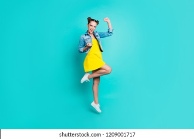 Full length body size of nice crazy positive glad stylish trendy girl with hair-buns, wearing short dress and denim jacket, showing winning gesture, isolated on green turquoise background