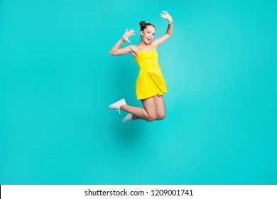 Full length body size of nice cute cheerful positive glad optimistic trendy attractive charming girl with hair-buns, jumping up in air in short dress, isolated on green turquoise background