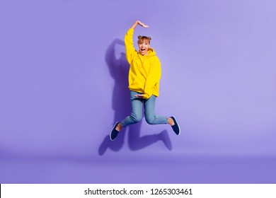 Full length body size photo of jumping high crazy she her lady with pretty buns hands disordered yelling in gladness wearing casual jeans yellow pullover isolated on purple background