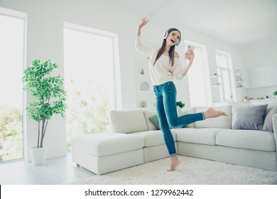 Full length body size photo of wonderful brunette she her lady headphones on ears dance sing out loud looking words of song in telephone glad wearing casual jeans white pullover