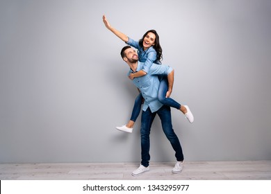 Full length body size photo funky cheer she her he him his lady guy piggyback ride walk meet adventures hand arm up run runner wear casual jeans denim shirts outfit clothes isolated grey background