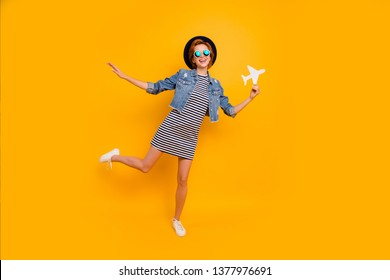 Full length body size photo beautiful foxy she her lady paper airplane traveler imagine flight wear specs vintage hat casual striped t-shirt dress jeans denim isolated yellow bright vivid background