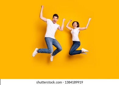 Full length body size photo funky she her he him his pair jumping high raised fists yell scream shout loud cheerleader football fans wear casual jeans denim white t-shirts isolated yellow background