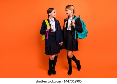 Full length body size photo two beautiful she her little ladies funny hands arms together ready first learn day wear formalwear shirt blazer skirt school form bag isolated bright orange background