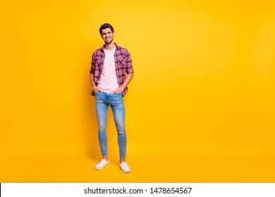 Full length body size photo of enjoying guy posing in front of camera while isolated with yellow background