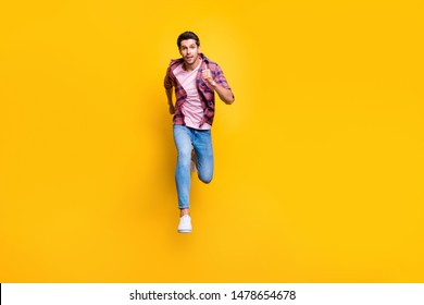 Full length body size photo of serious running man looking at camera moving towards it while isolated with yellow background