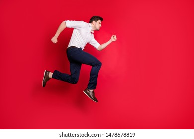 Full length body size photo of rapidly running man concentrated on some goal ahead while isolated with red background
