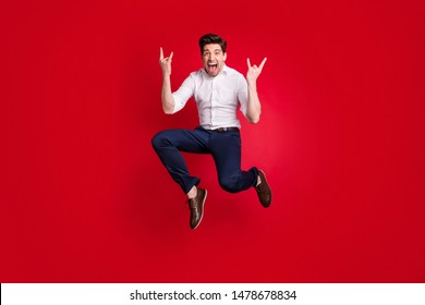 Full length body size photo of screaming shouting rock musician showing you rocker sign horned fingers while isolated with red background