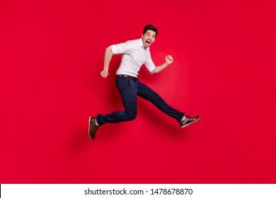 Full length body size photo of rejoicing excited ecstatic man running quickly rapidly fast while isolated with red background