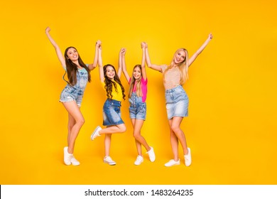 Full length body size photo of cheerful team of four members having great weekend and holidays wearing denim skirts outfit raising fists up isolated vibrant background
