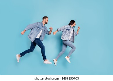 Full length body size photo of funny enjoying nice good cute couple wearing jeans denim clothes having contests at fast running while isolated with blue background