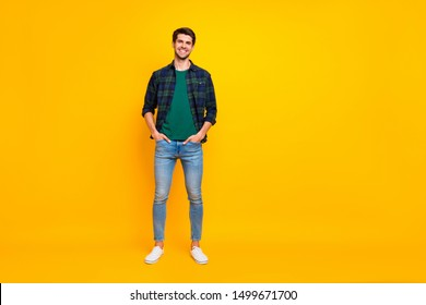 Full length body size photo of handsome man holding hands in jeans pockets wearing plaid shirt denim footwear stand isolated over bright color background standing posing confidently