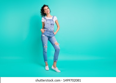 Full length body size photo of attractive funky girlfriend standing confidently with hands in jeans overall pockets smiling toothily isolated over turquoise vibrant color background