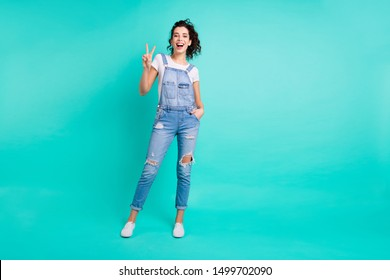 Full length body size photo of charming cute cheerful confident girlfriend with her hands in pocket of jeans overall saying you hi by showing v-sign isolated over turquoise vivid color background