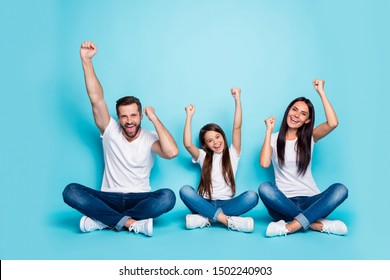 Full length body size photo of charming beautiful funny funky family rejoicing with their victory over someone wearing white t-shirts jeans denim while isolated with blue background
