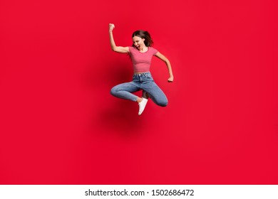 Full length body size photo of funky excited trendy stylish ecstatic rejoicing girlfriend student encouraged with victorious triumph wearing jeans denim striped t-shirt isolated red background