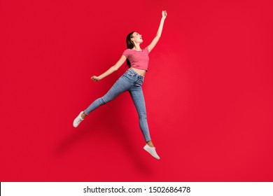 Full length body size photo of cheerful ecstatic positive charming beautiful girlfriend flying with umbrella trendy wearing jeans denim striped t-shirt while isolated with red background