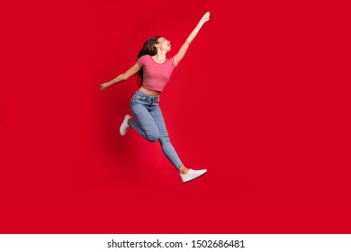 Full length body size photo of beautiful crazy cute stretching up to reach something while wearing jeans trendy denim striped t-shirt footwear while isolated with red background