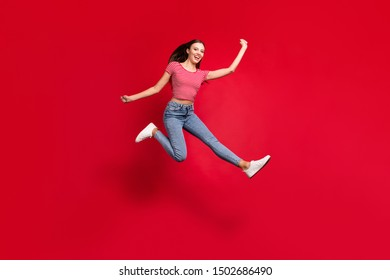 Full length body size photo of beautiful attractive ecstatic girlfriend hurrying towards mall excited while isolated with red background wearing jeans denim striped t-shirt
