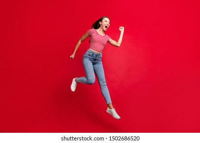 Full length body size photo of excited funky funny overjoyed rejoicing girlfriend running for sell out wearing jeans denim striped t-shirt while isolated with red background