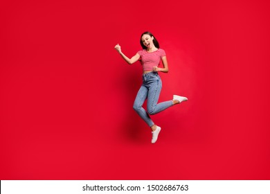 Full length body size photo charming cute fascinating nice girlfriend wearing jeans denim striped t-shirt winning something and rejoicing with it while isolated with red background