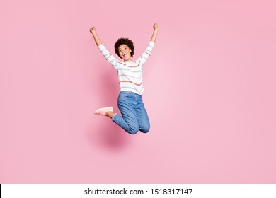 Full length body size photo of cheerful cute charming positive sweet pretty black millennial jumping up with happiness wearing jeans denim white striped sweater isolated pink pastel color background