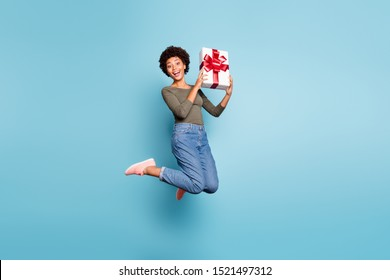 Full length body size photo of excited crazy cheerful nice positive ecstatic woman wearing jeans denim holding giftbox with hands jumping up isolated with vivid color blue background