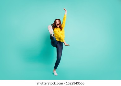 Full length body size photo of crazy ecstatic overjoyed cheerful cute nice childish girl wearing jeans denim footwear screaming loudly training fight skills isolated over teal vivid color background