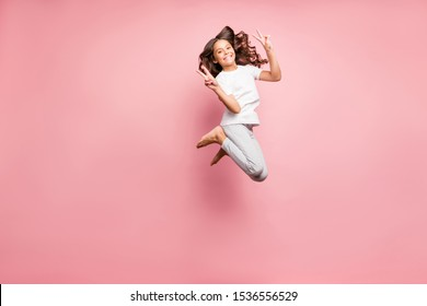 Full length body size photo of cheerful at leisure barefoot positive cute curly wavy preteen showing you double v-sign jumping up isolated pastel color background