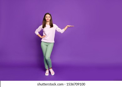 Full length body size photo of sweet cute pretty girl leaning on empty space laying her hand upon presentation standing confidently smiling toothily isolated over purple vivid color background
