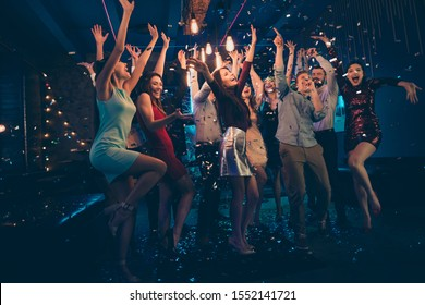 Full length body size photo of company dancing cheerfully at night club under falling confetti and light of shining lamps with smiles on their faces