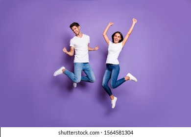 Full length body size photo of cheerful excited positive ecstatic jumping people in jeans denim white t-shit footwear expressing emotions isolated pastel violet color background