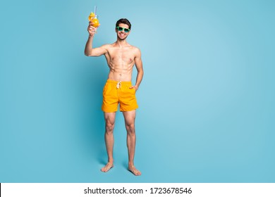 Full length body size photo of cheerful handsome attractive man with hand in yellow shorts pocket standing near ocean isolated pastel blue color background